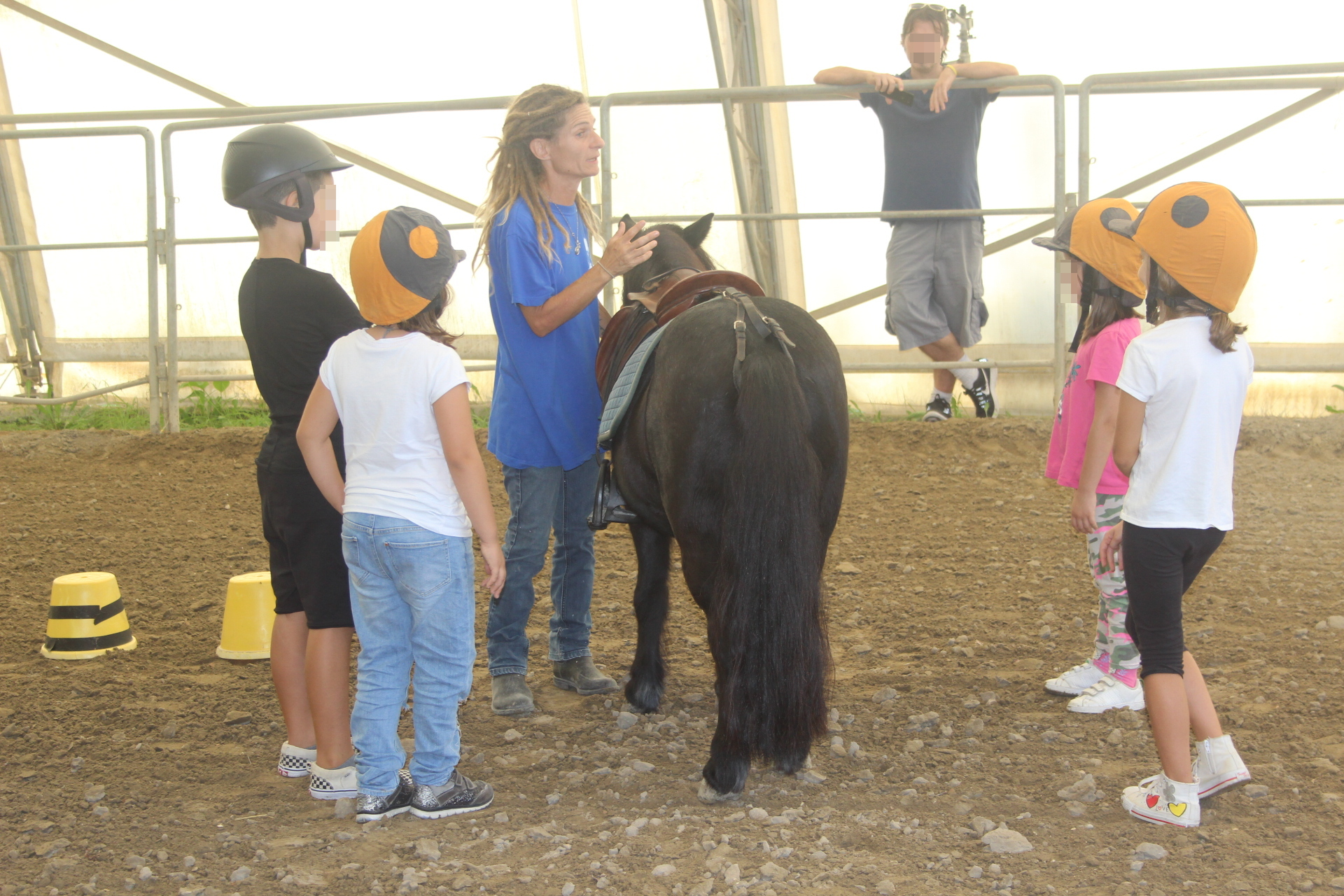 Bambini con un pony durante la lezione di Equitazione Etologica nel maneggio coperto della Scuderia Cento Fiori a Vallecchio di Montescudo, Rimini