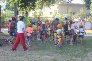 Bambini con casco e imbracatura che iniziano il percorso di apprendimento per le attrazioni di Rimini Avventura
